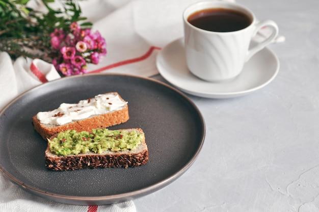 Здоровый и правильный завтрак. бутерброд с авокадо и домашним хлебом на закваске из зеленой гречки с семенами льна