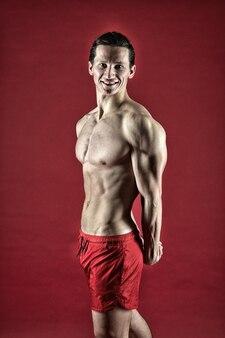 Здоровый и сильный. концепция мускулистого культуриста. развивайте себя. красавчик-мачо с мускулистым торсом. мускулистый спортсмен человек стоит уверенно. привлекательный парень с мускулистой грудью. горжусь отличной формой.