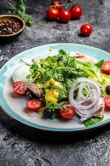 Полезный и вкусный салат из свежих овощей, пашот, яйца, лист салата, черри, помидоры, маслины и кукуруза. вертикальное изображение. вид сверху