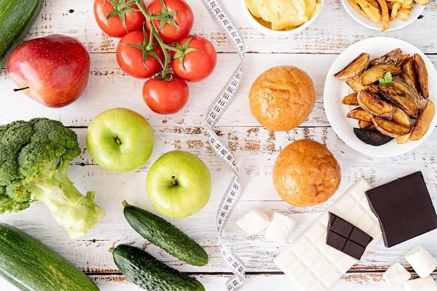 Концепция здорового и нездорового питания. фрукты и овощи против конфет и картофеля фри сверху лежат на деревянном столе