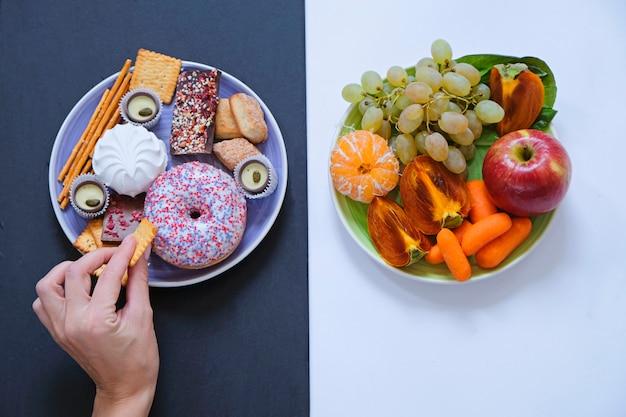 건강하고 건강에 해로운 음식 개념, 과일 및 야채 대 도넛, 과자 및 초콜릿.