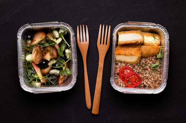 Концепция доставки здоровой и вегетарианской еды. свежий салат и гречневая каша с сыром.