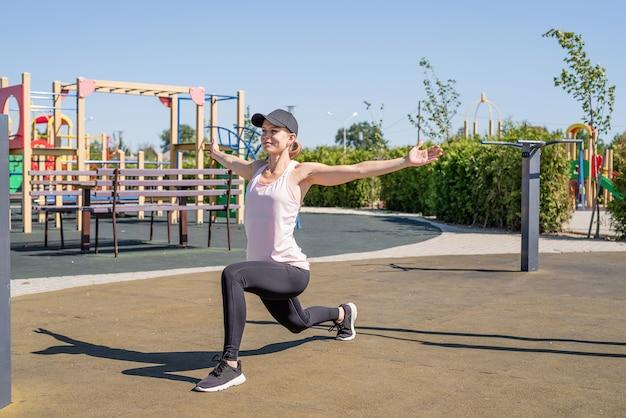 건강하고 활동적인 라이프 스타일. 스포츠 및 피트니스. 화창한 여름날 운동장에서 운동하는 운동복을 입은 행복한 여성, 워밍업
