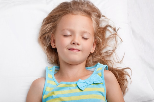 Healthy appealing little girl with long messy hair, keeps eyes shut, dressed in pajamas, has pleasant dreams during night rest, lies on white bed. small child has healthy sleep. rest concept