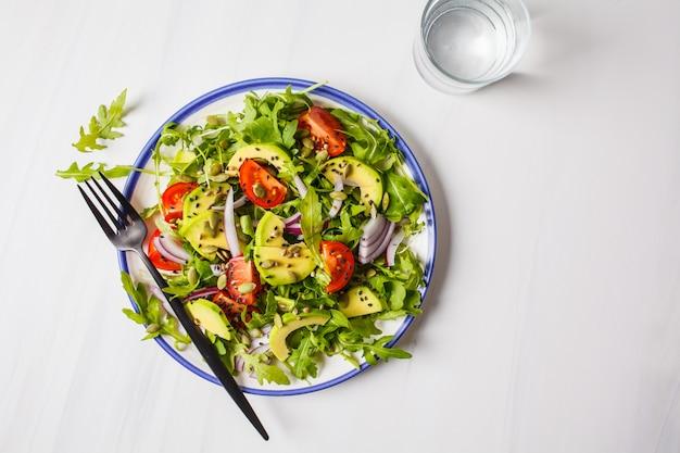 Healthy arugula, avocado, tomatoes salad on white marble background.