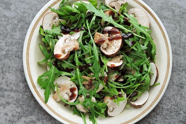 Здоровый салат с рукколой и сырыми шампиньонами с оливковым маслом и соевым соусом веганский салат с сырыми грибами.