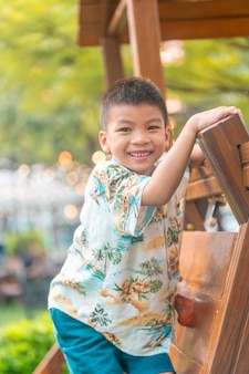健康で幸せな子供のコンセプトのために公共公園の木の遊び場の頂上に登る健康なアジアの少年