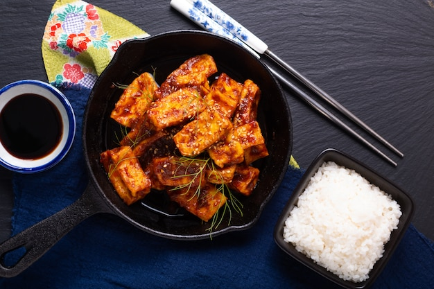 Healthy asian food concept homemade stirs fried spicy chili sauce, organic tofu in skillet iron pan with copy space