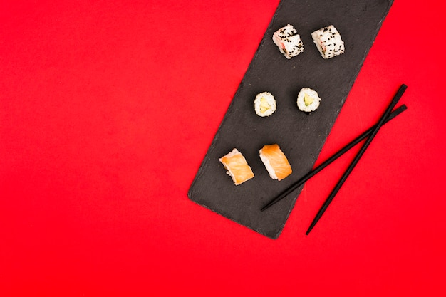 Healthy asian rolls and chopsticks over slate stone on red surface