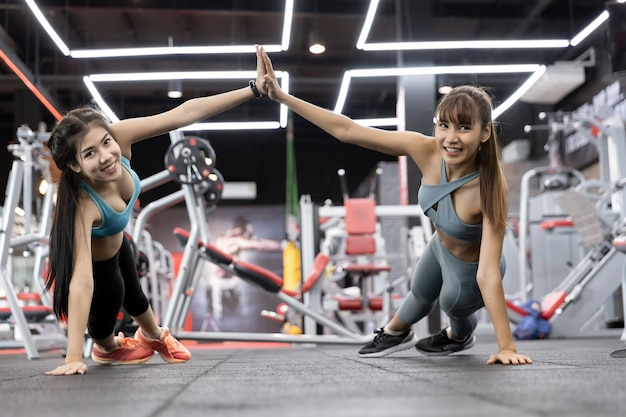 Healthy asian two people young woman push-up on weights and giving high five