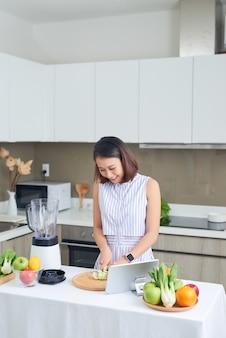 Здоровая азиатская женщина любит делать очищение от токсинов из зеленых овощей и смузи из зеленых фруктов с блендером на кухне дома. концепция диеты. здоровый образ жизни