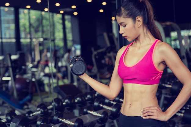Healthy asian woman workout in gym, beauty teenage girl lifting weights training with sportswear