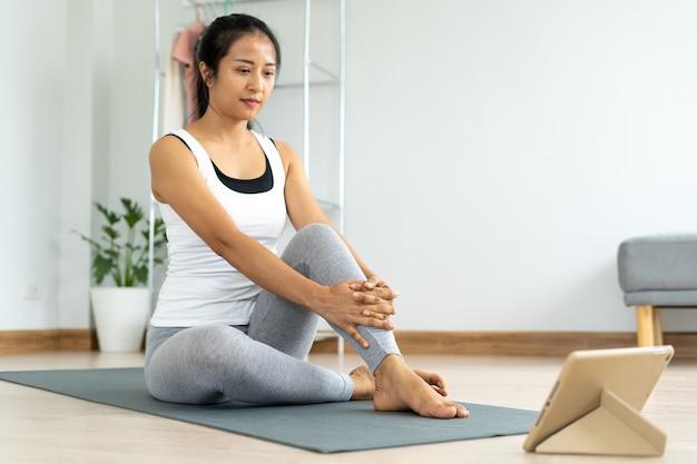 健康なアジアの女性は、タブレットを介してエクササイズクリップを見ています。