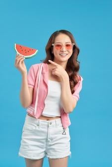 健康なアジアの若い女性はスイカを食べる、
