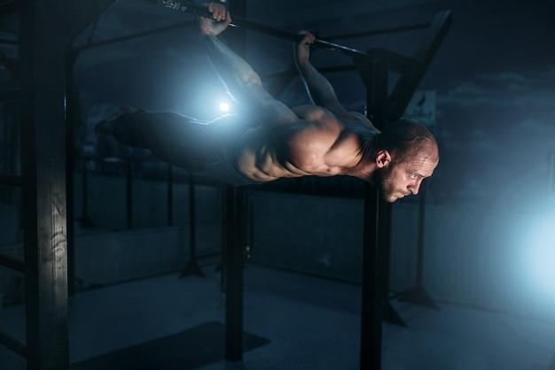 Здоровый спортсмен с мускулистым телом, прилагающий усилия, чтобы сохранить горизонтальное равновесие.