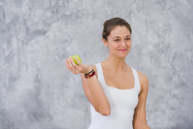 Здоровая спортивная (ый) спортивная женщина ест зеленое яблоко