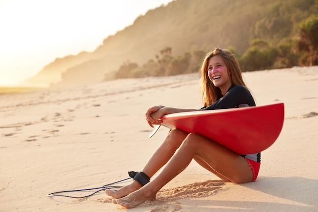 幸せな表情で健康なアスリート女性、細い脚を持ち、レクリエーションとひもでサーフィンを楽しんでいます