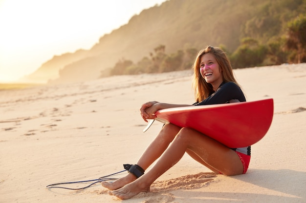 Healthy athletic woman with happy expression, has slender legs, enjoys recreation and surfing with leash