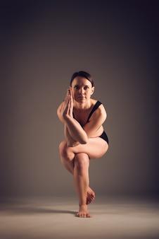 暗い壁でガルーダサナをやっている健康な運動の若い女性のヨガ愛好家。関節の弛緩と腰痛の緩和の概念。