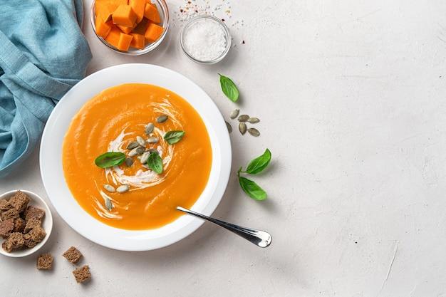 明るい灰色の背景にカボチャの種とクリームと健康的な秋のカボチャスープ