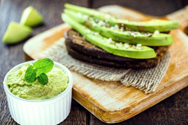 Healthy avocado toast with rye bread, slices of avocado, arugula, and seeds.