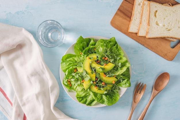 Полезные тосты из авокадо на завтрак или обед с хлебом, ломтиками авокадо, рукколой, тыквой и семенами кунжута, солью и перцем. вегетарианские бутерброды. растительная диета. концепция всей еды.