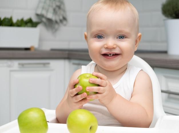 キッチンの子供の椅子に座っている健康な男の子の大きな青い目は青リンゴを食べます。
