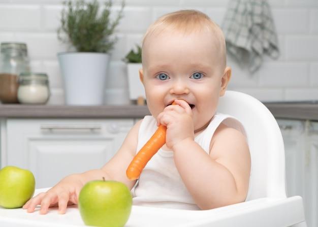 キッチンの子供の椅子に座っている健康な男の子の大きな青い目はオレンジ色のニンジンを食べます。