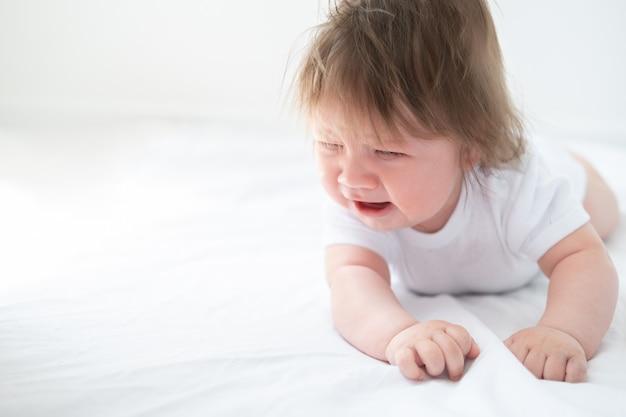 家で泣いて白い寝具の上に横たわっている健康な男の子。