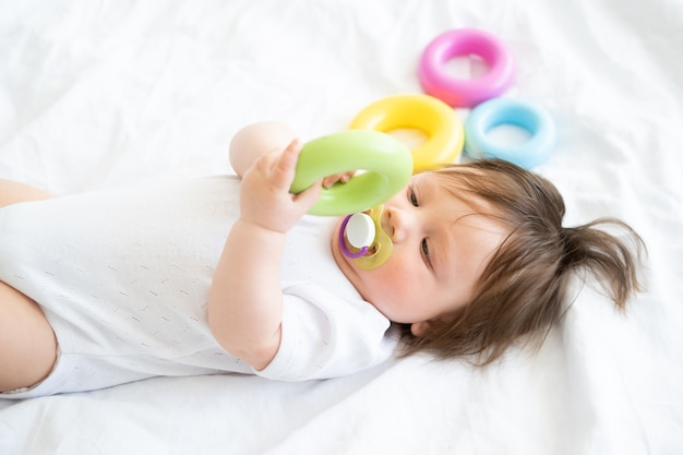 Здоровый мальчик лежал на кровати и играл с красочной пластиковой игрушкой круга.