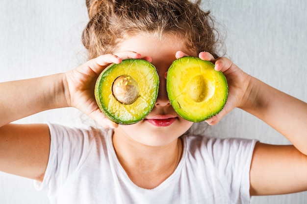 Healthy baby food concept, girl child holds sliced avocado in place of the eyes,