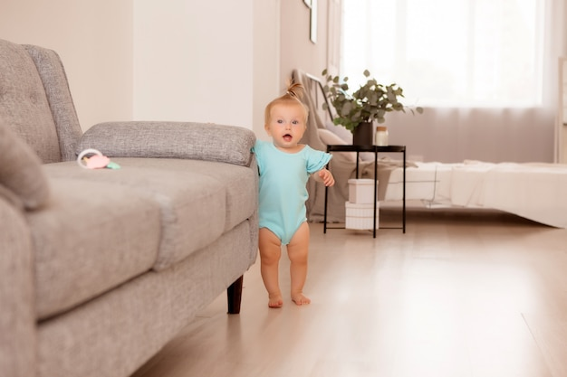 Healthy baby girl in a room next to a gray sofa is learning to walk