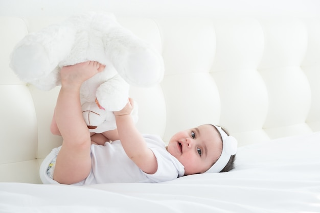 Healthy baby girl in a white bodysuit lying on a bed on white bedding with teddy bear
