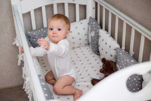 Healthy baby in white clothes is sitting in a child's bed