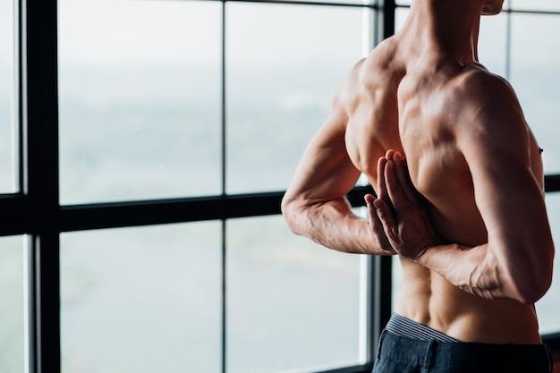 健康な背中と背骨。効果的なヨガトレーニング。スポーツとフィットネス。ジムでアーサナを行使する男。