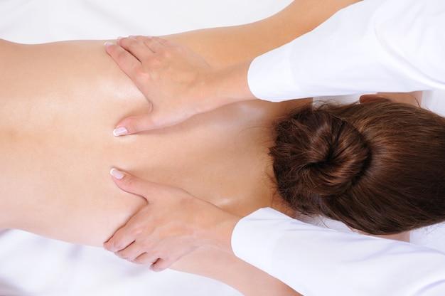 Здоровый массаж спины для молодой женщины - белый фон