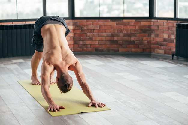 Healthy back and spine thanks to yoga. sport and fitness. man exercising downward dog asana in gym.