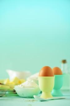 健康的なベーキング成分 - バター、砂糖、小麦粉、卵、油、スプーン、ブラシ、泡立て器、青い背景にミルク。バナー。
