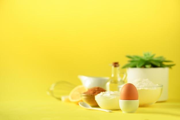 健康的なベーキング成分 - バター、砂糖、小麦粉、卵、油、スプーン、ブラシ、泡立て器、黄色の背景上のミルク。