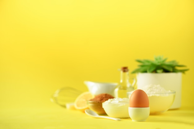 Healthy baking ingredients - butter, sugar, flour, eggs, oil, spoon, brush, whisk, milk over yellow background.