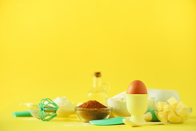 Healthy baking ingredients - butter, sugar, flour, eggs, oil, spoon, rolling pin, brush, whisk, milk over yellow background.
