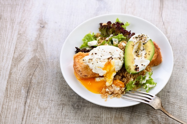 A healthy and balanced breakfast . benedict's egg spreads on a toasted toast with half an avocado, quinoa and lettuce, seasoned   spices and yogurt dressing.