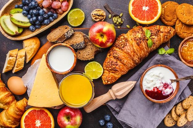 Healthy balanced breakfast on a dark background. muesli, milk, juice, croissants, cheese, biscuits.