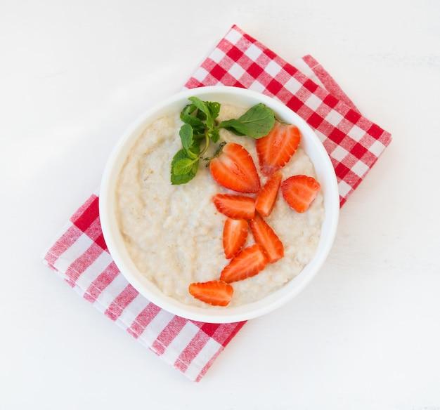 Здоровый сбалансированный завтрак из овсянки с клубникой и медом на белой стене. горизонтальное фото. вид сверху