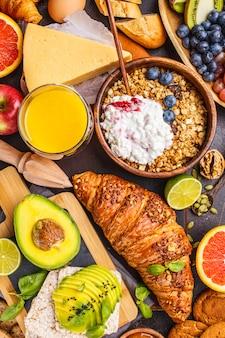 Здоровый сбалансированный завтрак на темном фоне. мюсли, молоко, сок, круассаны, сыр, печенье.