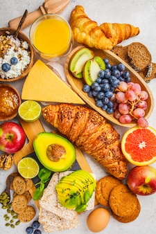 Healthy balanced breakfast on white background. muesli, juice, croissants, cheese, biscuits and fruit, top view.