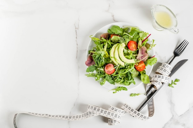 Healthy balanced diet concept, weight loss, calorie counting. plate with green salad leaves, tomatoes, avocado with yogurt dressing, white table, with fork, knife, measuring tape, top view copyspace