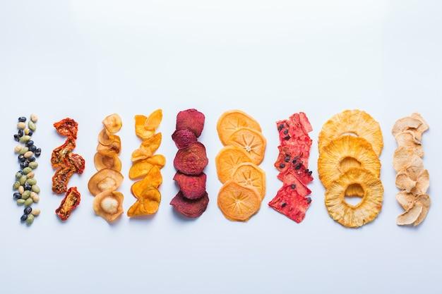 건강에 좋은 균형 잡힌 음식, 깨끗한 식사, 자연적으로 맛을 낸 스낵, 투명한 재료 개념. 말린 과일과 야채, 흰색 배경에 탈수 칩