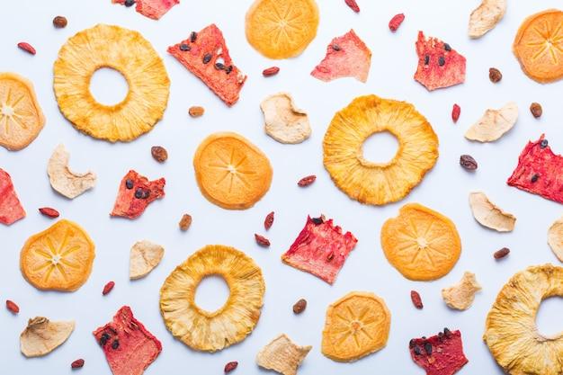 건강에 좋은 균형 잡힌 음식, 깨끗한 식사, 자연적으로 맛을 낸 스낵, 투명한 재료 개념. 흰 바탕에 말린 과일, 탈수된 감, 수박, 파인애플, 사과 칩