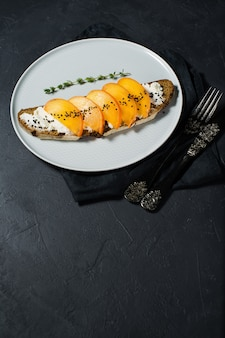 Healthy balanced food sandwich with persimmon and soft cheese